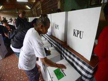 Seorang pengundi wanita membuang undi di pusat undian terletak di daerah Kuta, Bali ketika Pemilu 2109 yang berlangsung hari ini. - Foto AFP