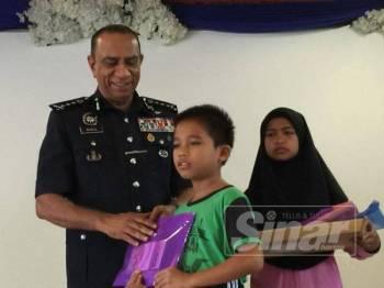 Mohd Khalil menyampaikan sumbangan kepada seorang pelajar SK Polis Kem, Kulai hari ini.