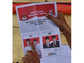 Petugas di TPS di Jakarta sedang mengira undi. - Foto: AFP