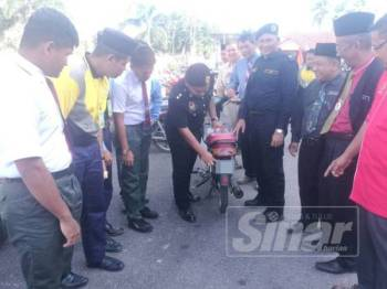 Che Mohd Hisham (empat dari kiri) memeriksa sebuah motosikal yang menggunakan nombor pendaftaran kecil tidak mengikut spesifikasi dalam pemeriksaan di sebuah sekolah menengah di Jertih hari ini.