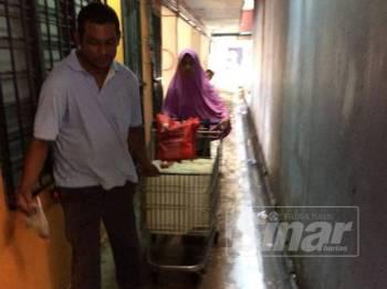 Penduduk mengangkut tadahan air menggunakan troli ke rumah mereka.
