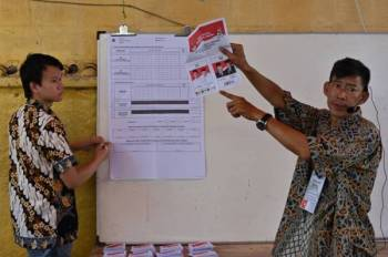 Pegawai pilihan raya mengira undi di hadapan saksi di pusat pengundian di Jakarta. - Foto: AFP