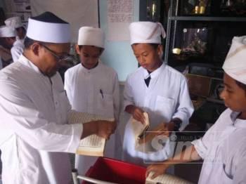 Fadzli (kiri) menunjukkan kaedah melupuskan al-Quran kepada pelajar Tahfiz Madrasah Tahfizul Quran al-Furqan.