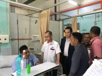 Boon Chye (dua dari kiri) berbual dengan salah seorang pesakit ketika melawat Hospital Kampar.
