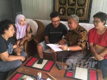 Alvin (tengah) menunjukkan dokumen berkaitan laporan kesihatannya kepada kumpulan Prestij Melaka sambil diperhatikan isterinya, Ann Lucia Sta Maria, 51 (kiri sekali) di rumahnya di Kampung Portugis, Ujong Pasir, Melaka.