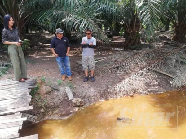 Lay Peng (kiri) ketika melakukan tinjauan mendapati warna sungai telah menjadi hitam dan tiada lagi ikan hidup dalam sungai, di Kampung Jenjarom.