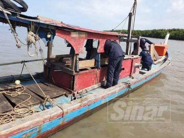 Anggota Maritim melakukan pemeriksaan terhadap bot nelayan yang ditinggalkan selepas dua nelayan terjun ke laut melarikan diri, awal pagi tadi. Foto: Maritim