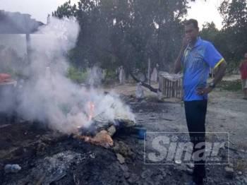 Yogeswaran menutup hidung kerana tidak tahan bau busuk akibat perbuatan membakar bangkai ayam dalam sebuah kebun di Pajam, semalam.