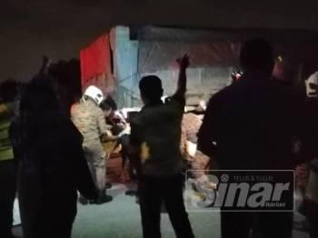 Anggota bomba mengeluarkan mangsa yang tersepit di bawah lori tanah
