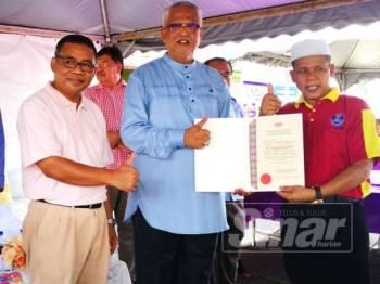 Mahfuz (dua dari kanan) menyerahkan sijil penghargaan kepada wakil pengerusi KRT Kampung Alor Gandak selaku penganjur bersama program.