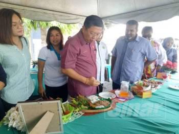 Kok Yew (tiga dari kiri) sempat merasa kerabu yang dipertandingkan sempena program Rapat Rakyat di Dewan Jitra, semalam.