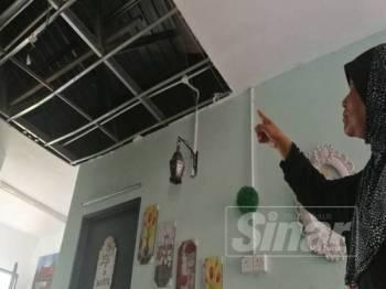 Che Minah menunjukkan bahagian siling rumah yang jatuh dalam kejadian Ahad lalu di Kampung Pahi.