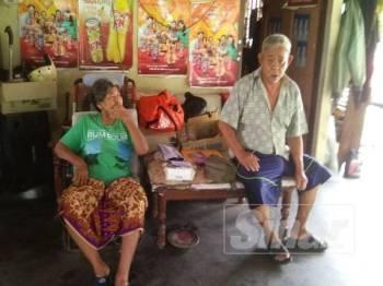 Rosli (kanan) dan Faridah berteduh di bangsal tokong setelah dihalau keluar dari rumah mereka.