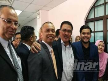 Abdul Latif (tengah) bersama anaknya, Ahmad Fauzan (dua dari kanan) dan Amir (dua dari kiri) ceria selepas hakim membaca keputusan di Mahkamah Sesyen Johor Bahru, hari ini.