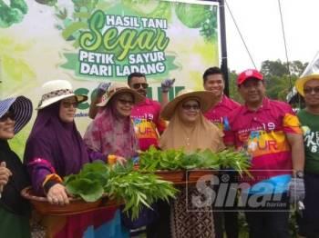 Siti Mariah (tiga dari kanan) menunjukkan sayuran yang dipetik terus dari Kebun Komuniti Lapan Timur, Seksyen 8 semalam.