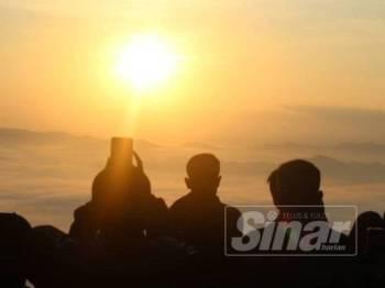 Pelancong mengambil peluang menyaksikan matahari terbit di puncak Air Terjun Jelawang yang terletak di Kem Baha.
