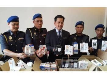 Saharuddin (tengah) menunjukkan sebahagian barangan yang berjaya dirampas KPDNHEP Terengganu
