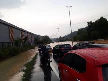 Pengguna jalan raya terpaksa menunggu dan ada yang berpatah balik apabila persimpangan tiga berhampiran Alam Budiman dilanda banjir kilat. (Gambar ihsan orang ramai)
