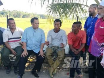 Husam (tiga, kiri) mendengar permasalahan pesawah di bendang Kampung Wakaf, semalam.