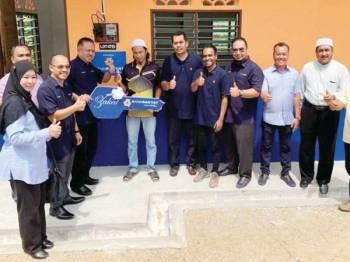 Mohd Zaki Yamani (empat dari kiri) menerima replika kunci yang diserahkan Syed Nasser Hussain (tiga dari kiri) sewaktu Majlis Penyerahan Kunci Rumah Asnaf Bank Rakyat di Kampung Pasir Dula.