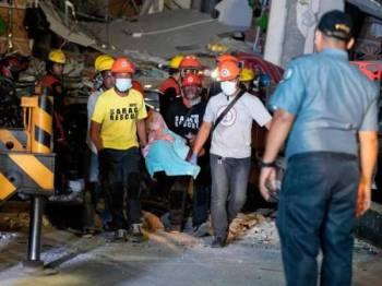 Anggota penyelamat membawa keluar mangsa dari bangunan runtuh di bandar Porac, wilayah Pampanga. - Foto AFP