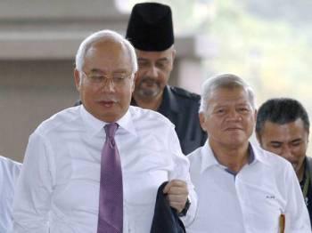 Najib  (kiri) tiba di Kompleks Mahkamah Kuala Lumpur hari ini bagi perbicaraan kes yang dihadapinya membabitkan dana SRC International Sdn Bhd berjumlah RM42 juta. - Foto Bernama
