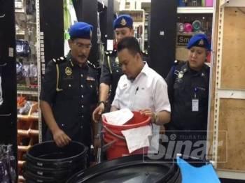 Muhamad Zikril (dua dari kanan) memeriksa harga tong air menerusi operasi yang dijalankan di Puchong hari ini.