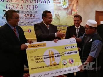 Wakil Iman Care & Warga Cakna (dua kanan) menyerahkan sumbangan kepada Ahmad Samsuri (dua kiri), sambil diperhatikan Pengarah PAS Relief, Muhammad Sanusi Md Nor (kiri).
