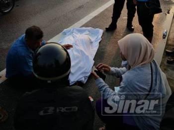 Kelihatan suami mangsa memangku mayat isterinya selepas disahkan meninggal dunia di tempat kejadian.