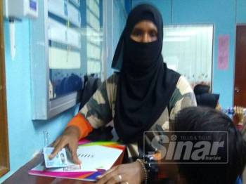 Siti Zahida terharu melihat surat beranak berstatus warganegara yang diperolehi anak-anaknya.
