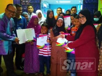 Mas Ermieyati (dua dari kanan) dan Norazlee (kiri) ketika menyerahkan surat beranak kepada 12 ahli keluarga yang selama ini tidak pernah mendaftarkan kelahiran anak mereka di JPN. (blur muka)