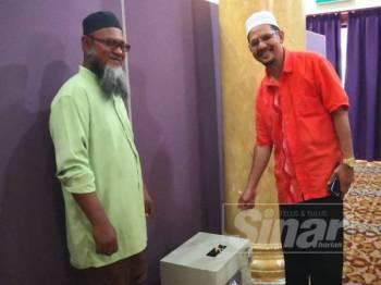 Mohd Arif (kiri) dan Baharuddin menunjukkan tabung masjid yang menjadi sasaran pencuri berkenaan.