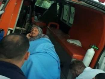 Wanita warga emas Palestin, Khadra Salman Rib'ey dimasukkan ke dalam ambulans selepas terkena kelongsong gas pemedih mata yang dilepaskan tentera Israel di bandar Yatta, semalam.