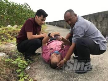 Ahmad Amzad (tengah) dibantu pegawainya selepas terjatuh pagi tadi.
