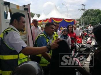 Saifuddin (tengah) membantu pengguna motosikal mengisi minyak di Stesen minyak Shell