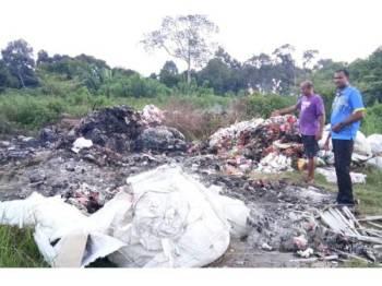Yogeswaran (kanan) melihat tempat pembuangan sampah haram di Mantin semalam.
