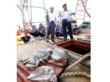 Muhammad Suffi (kanan) dan Ahli Parlimen Kuala Terengganu, Ahmad Amzad Hashim menunjukkan sebahagian hasil hasil laut yang dirampas daripada enam bot berkenaan.