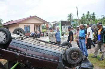 Abdul Yunus (kiri) meninjau keadaan ribut melanda rumah Rosnan (tiga dari kiri) dan menyebabkan kereta miliknya terbalik di Kampung Parit Mat Ali Tengah, Kuala Kurau, semalam.