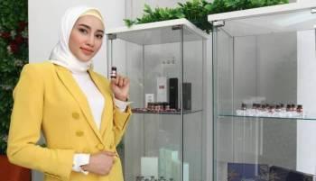 Eira bersama produk Ruby-Cell yang berfungsi membantu merawat kulit wajah wanita