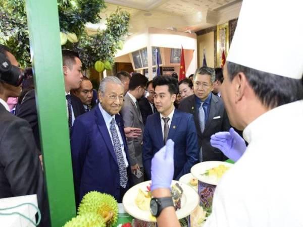 Tun Mahathir (tengah) berkesempatan merasa durian hasil daripada sistem pertanian pintar.