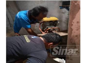 Kerja-kerja membersihkan telaga di rumah Khalijah Awang, 75, selepas mangsa mengadu pening dan lemau.
