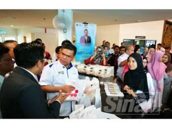 Saifuddin mengagihkan pek makanan kepada pelajar golongan B40 pada pelancaran Food Bank Siswa Malaysia di UniSZA.