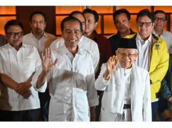 Jokowi (tengah) bersama pasangan regunya, Ma'ruf Amin dilaporkan mendahului keputusan berdasarkan 50 peratus kiraan undi.