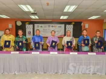 Anuar (tengah) bersama enam wakil kolej vokasional memeterai persefahaman dengan Kolej Universiti TATI (TATIUC).