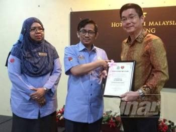 Tunku Shahrain (tengah) menyerahkan penghargaan kepada Kok Lim (kanan) pada majlis perasmian Program Perasmian Seranta Perkeso Taiping 2019 di sebuah hotel di Taiping hari ini.
