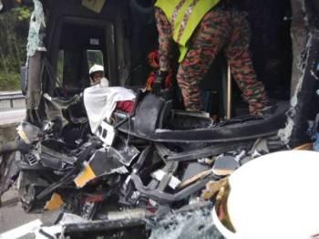 Anggota bomba melakukan kerja-kerja mengeluarkan mayat pemandu bas yang tersepit. FOTO- IHSAN BOMBA