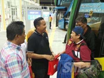 Mohd Rashidi (tiga, kanan) bergambar bersama penumpang terawal yang tiba di terminal tersebut.