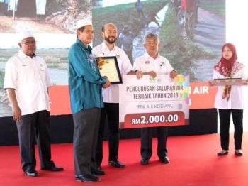 Mukhriz (tiga dari kanan) menyampaikan anugerah pengurusan saluran air terbaik 2018 kepada wakil PPK A-II Kodiang pada majlis itu. - Foto: Facebook Mukhriz Mahathir FC