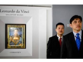 Gambar yang diambil pada 13 Oktober 2017 menunjukkan Jerry Chun Shing Lee (kanan) pada upacara membuka tirai lukisan Salvator Mundi, karya pelukis tersohor, Leornardo da Vinci di bilik pameran rumah lelong Christie di Hong Kong.