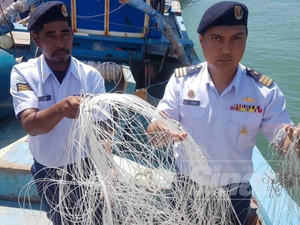 Rashidilhadi (kanan) dan pegawainya mrnunjukkan rawai yang dirampas dari salah sebuah bot yang ditahan.